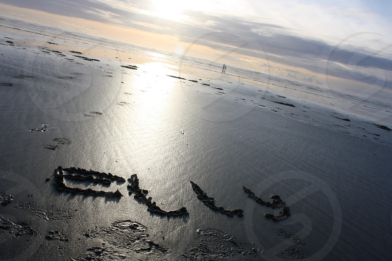 Writing names in the sand on the beach.   photo