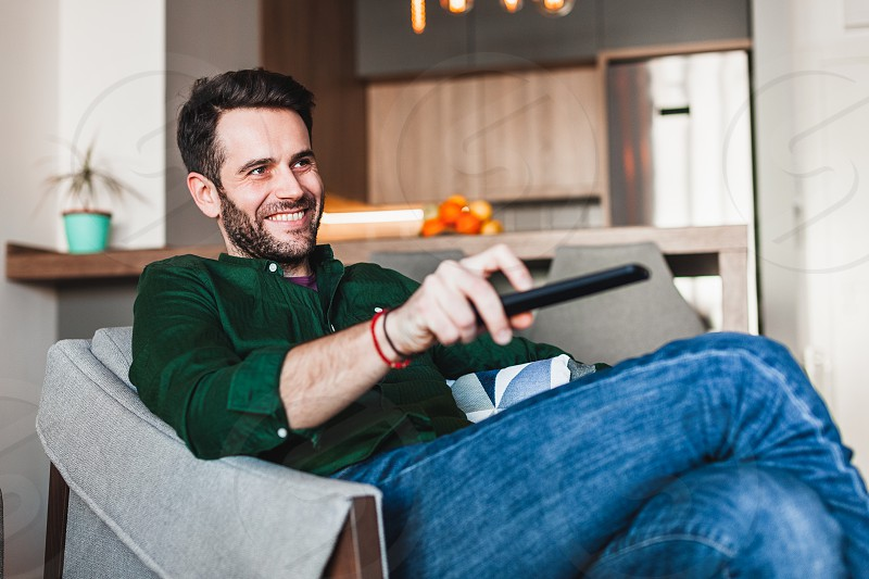 Young man holding remote controller watching tv  photo