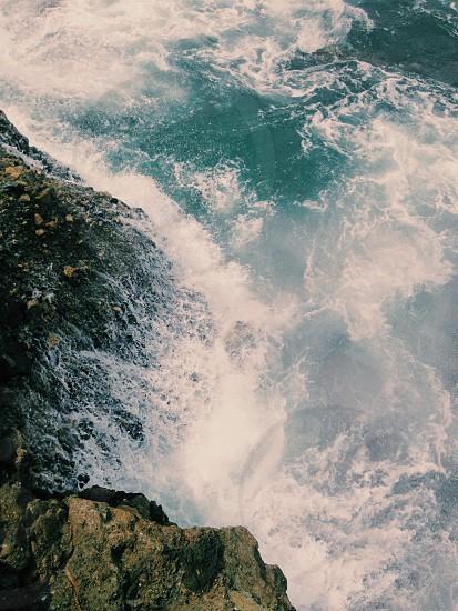 ocean waves splashing against cliffs photo