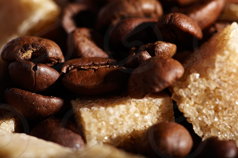 Coffee beans background with brown sugar cubes. Natural morning sunlight. photo