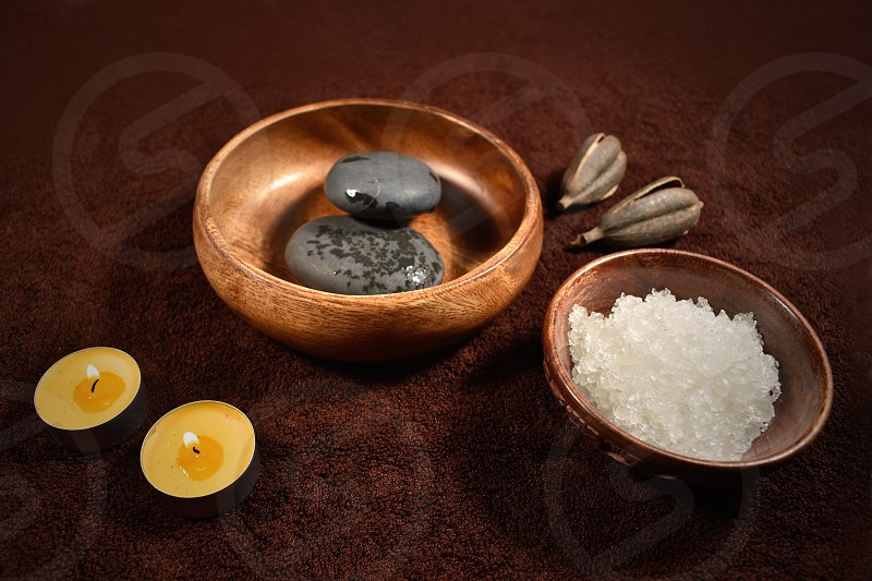 Brown wellness set. Wellness setting. Sea salt in bowl lava stones and candles on a brown textured background. Wellness brown background. Spa still life images photo