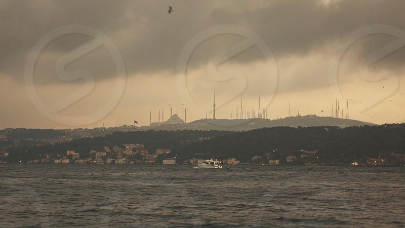 Picturesque seascape to a historical part of old sity Istanbul with antique mosque in a sunlight at sunset sky. photo
