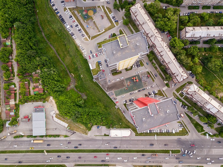 Aerial top view of two tall skyscrapers of red and yellow colors among small buildings with parking for cars and a children's playground in the yard with green trees and shrubs photo
