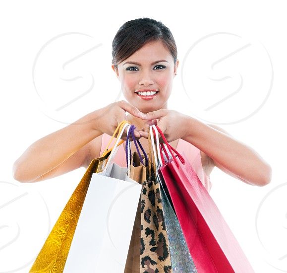 Portrait of happy woman holding shopping bags on white background photo