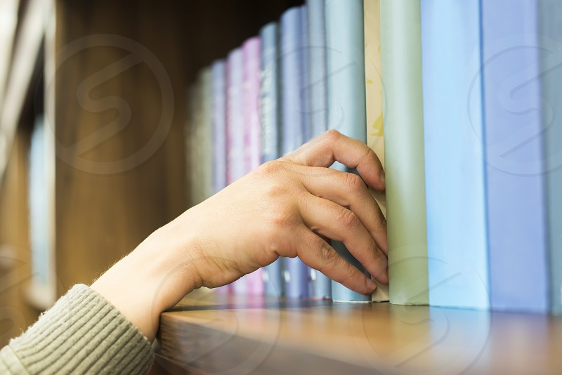 Hand pulling a book off the shelf. Blue colors books photo