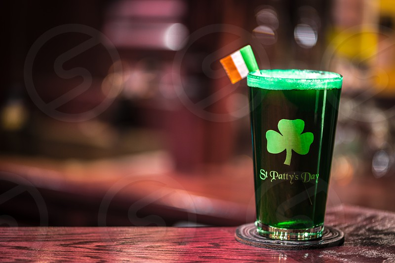 Glass of green beer with a shamrock and Irish flag sitting on a bar in a pub. photo