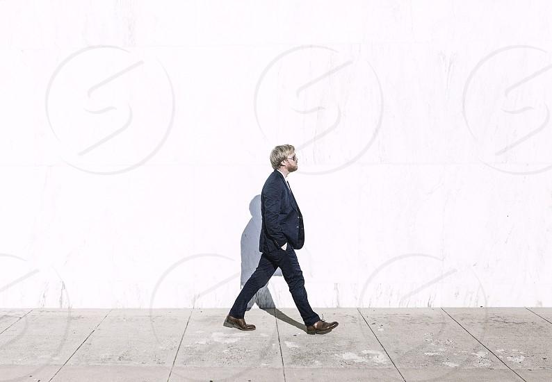A man in a suit walking on a sidewalk.  photo