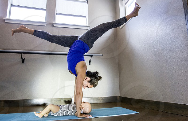 Mother and yogi practices hand stands with her baby boy in Boulder Colorado photo