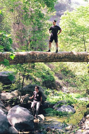 man standing on a tree trunk bridge photo