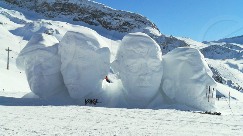 four men's faces sculpted in white snow photo