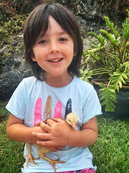 little boy holding a chicken photo
