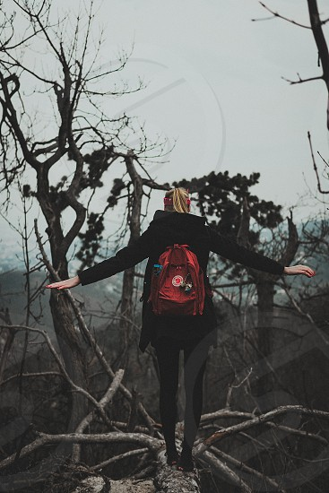 Blonde girl with red backpack is walking on a tree in summer and got framed in the middle.  photo