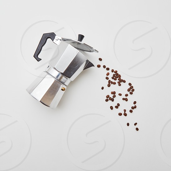 Fragrant coffee beans and metal coffee maker. Composition in the form of a pouring coffee on a white background with copy space. Flat lay photo