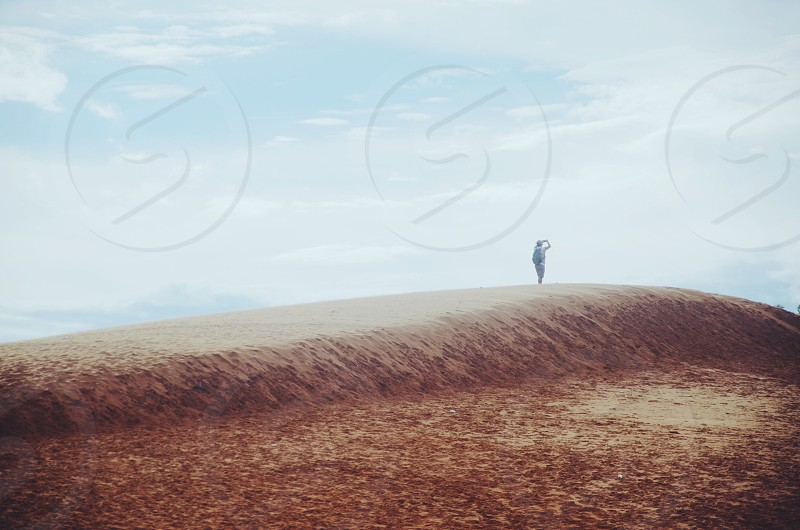 man standing on brown field photo