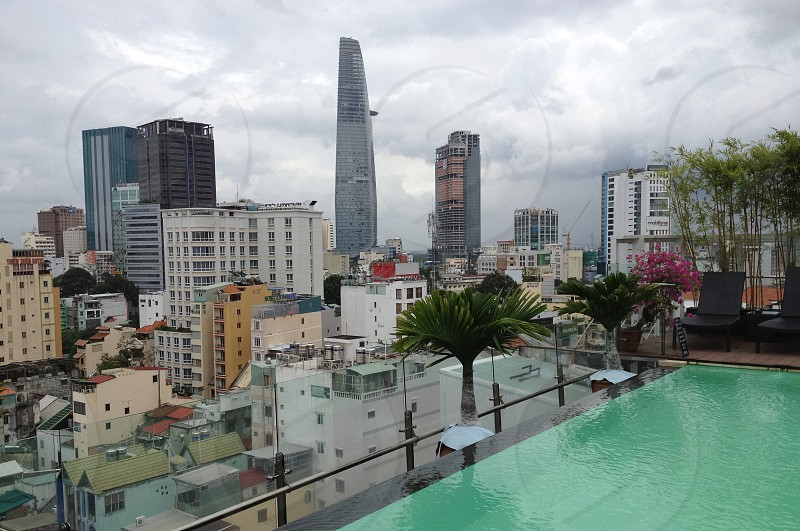 cityscape green trees and swimming pool under white and gray clouds photo