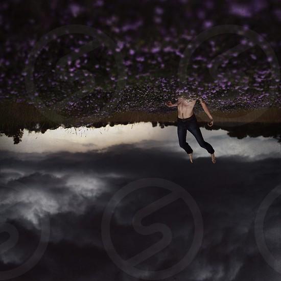 man in black denim jeans diving on flower field photo