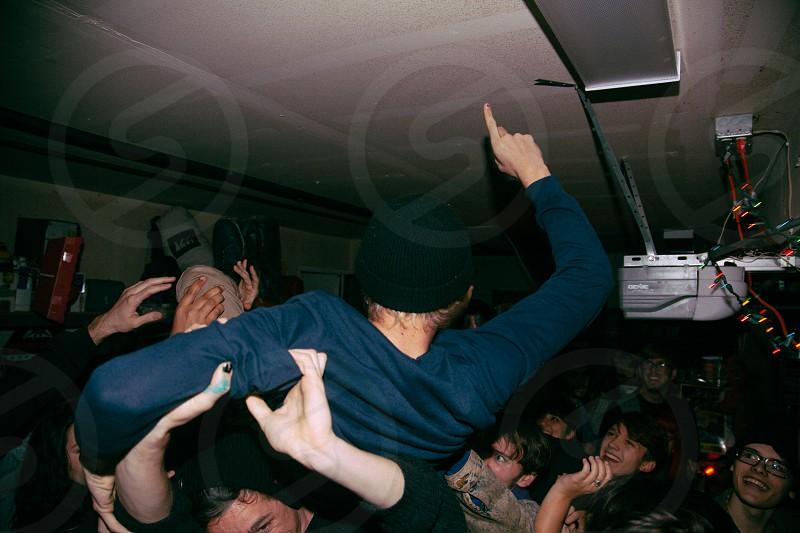 man in blue shirt crowd surfing in jam pack club photo