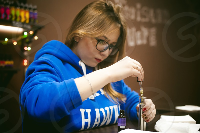beautiful young woman with glasses smoking electronic cigarette. girl in a blue sweater brings to his lips red box mod sitting indoors vape shop cafe photo