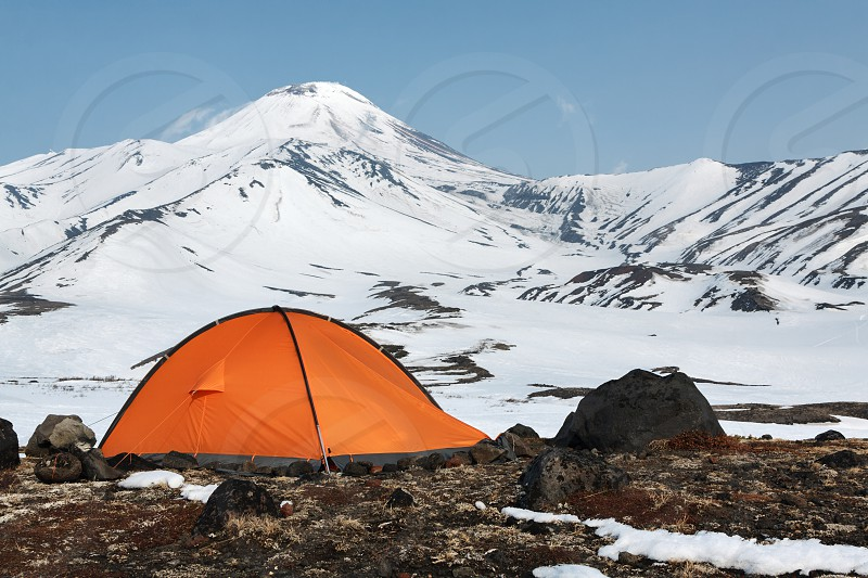 Outdoor camping (tourist tent) on meadow surrounded by snow in mountains on background of majestic cone of active of Avachinsky Volcano on Kamchatka Peninsula in Far East of Russia. photo