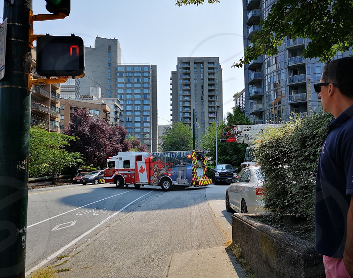 firetruck leaving the firep station while a pedestrian waits in Canada photo