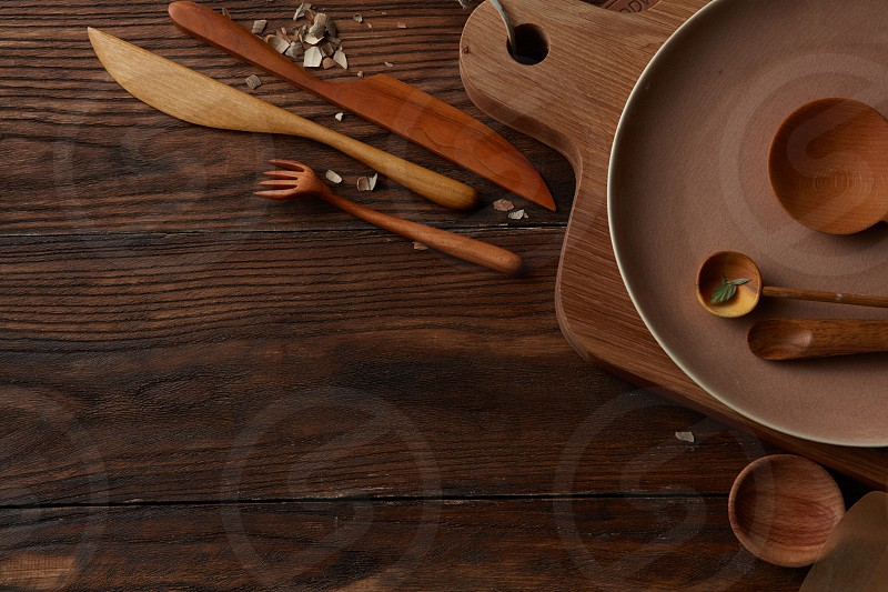 Plank with baking parchment in kitchen. Composition of kitchen devices represented on wooden table. Kitchen devices concept. photo