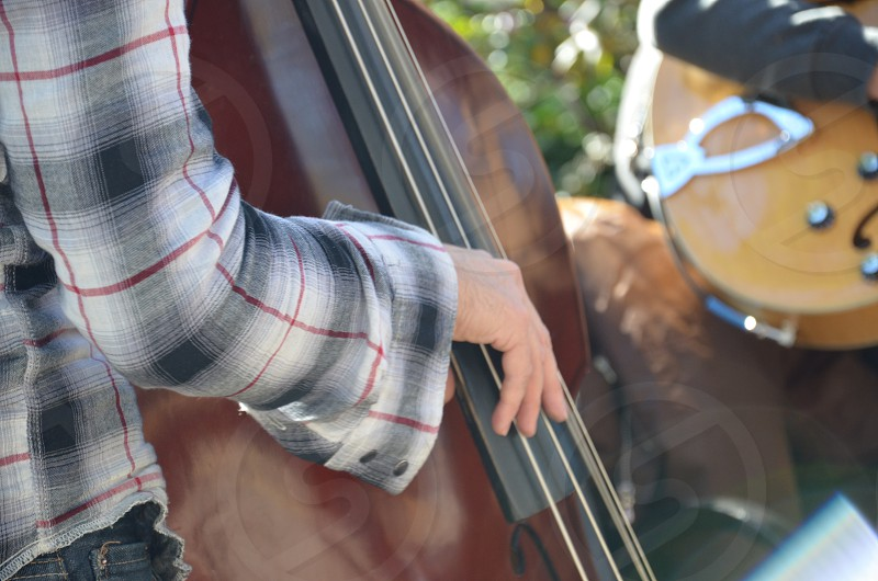 person wearing black and white long sleeve shirt playing cello photo