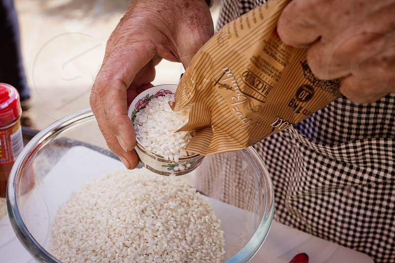 rice hands bowl arroz cooking prep pour pouring measure measuring spanish chef cook  photo