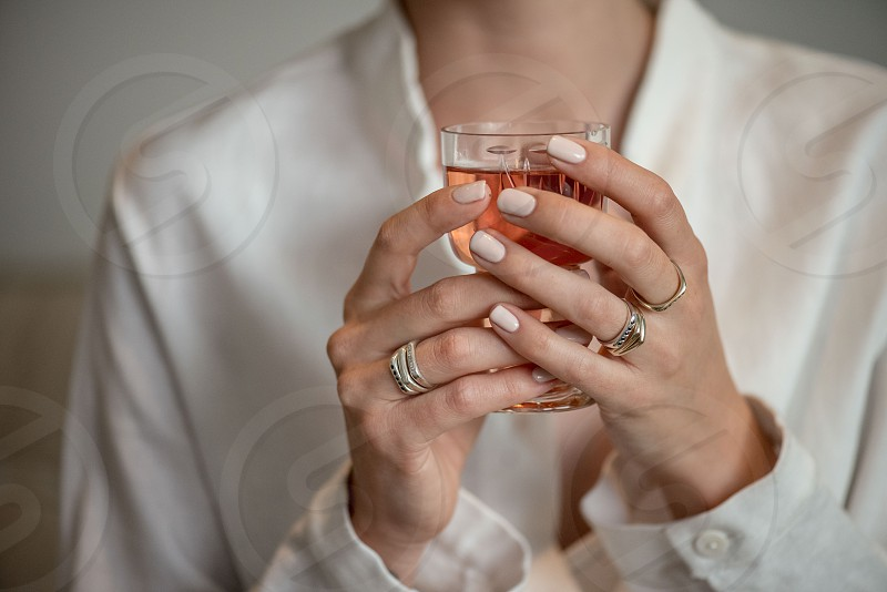 A woman drinks wine dressed elegantly and wearing jewellery. photo