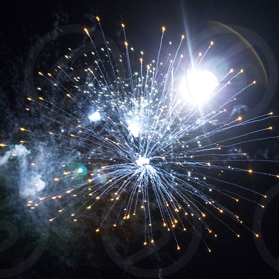Blue fireworks burst with smoke and lens flare photo
