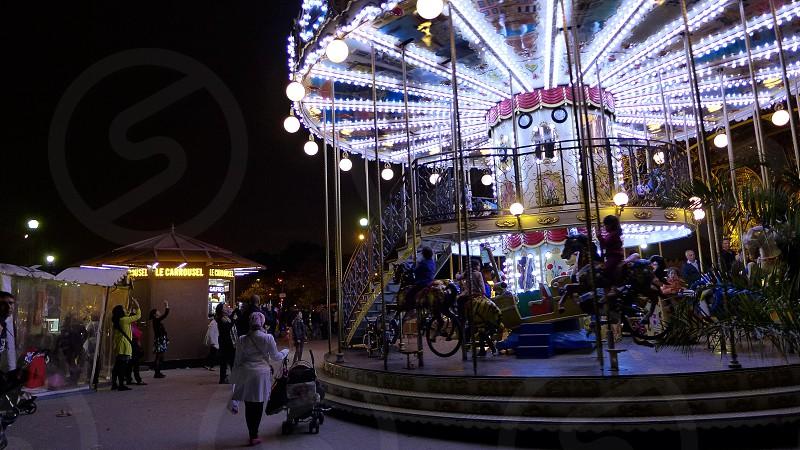 kids riding carousel on amusement park photo