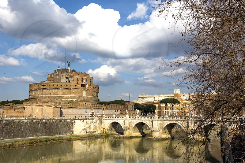 Castel Sant'Angelo viewed from Victor Emmanuel II bridge. The Mausoleum of Hadrian usually known as Castel Sant'Angelo (English: Castle of the Holy Angel) is a towering cylindrical building in Parco Adriano Rome Italy. It was initially commissioned by the Roman Emperor Hadrian as a mausoleum for himself and his family. The building was later used by the popes as a fortress and castle and is now a museum. The Castle was once the tallest building in Rome. photo