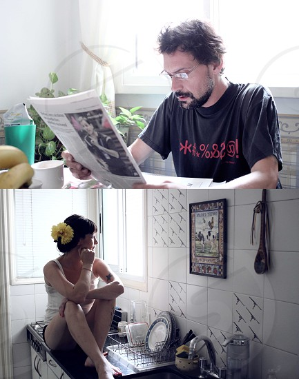 In the house husband reading newspaper wife in kitchen boring photo