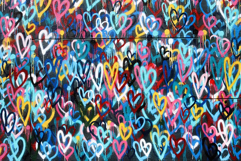 concrete wall with pink green red and yellow hearts graffiti photo