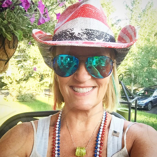 smiling woman wearing white blue and red USA-themed cowboy hat and black aviator sunglasses taking selfie photo