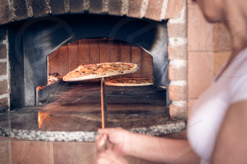 Woman making pizzas in restaurant's furnace. photo