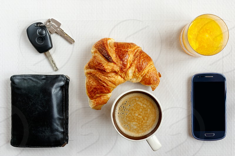 Morning : Almost ready to go : car and house keys wallet smartphone and a quick continental breakfast with orange juice a croissant and a cup coffee. photo