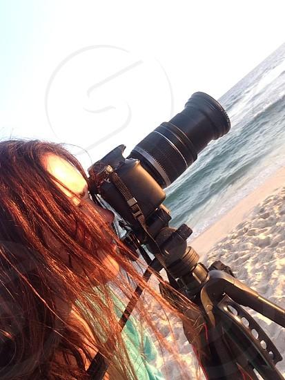 woman using black dslr camera with black tripod photo