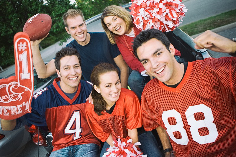 Tailgating: Group Of Football Fans Cheering For Team  people; Caucasian; happy; cheerful; smiling; toothy smile; man; male; woman; female; fan; football; jersey; friends; outdoors; 20s; party; tailgate; tailgating; tailgating party; sport; celebration; fun; holding; ball; cheering; pom pom; pom; yelling; excited; looking at camera; cheer; foam finger;  photo
