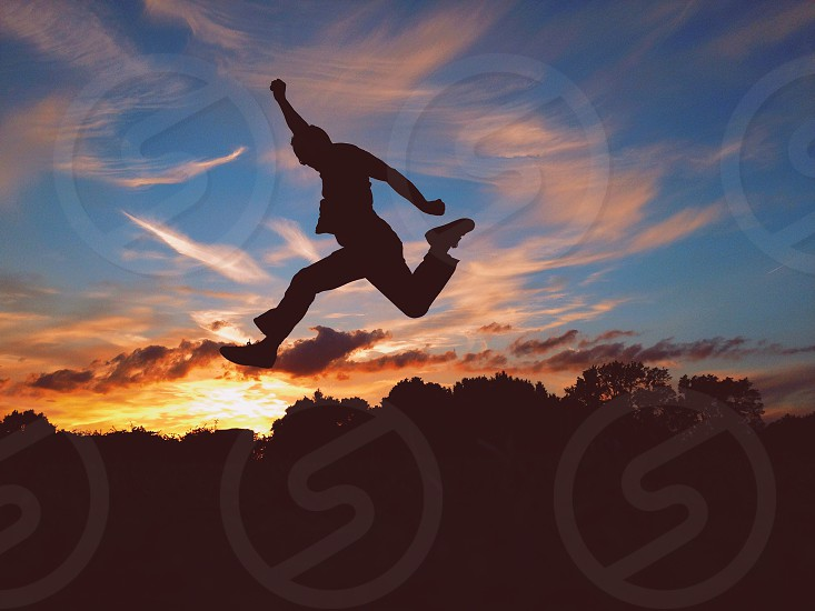 figure jumping arm raised silhouetted against sunset sky photo
