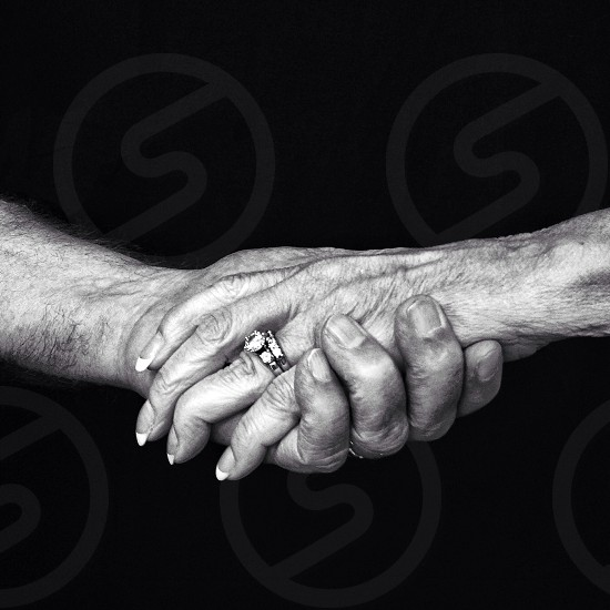 man and woman holding hands grayscale photography photo
