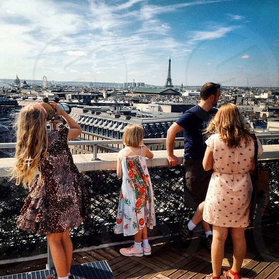 family standing on building balcony during daytime photo