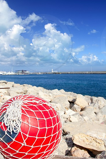 fishing red buoy with net in formentera port breakwater of Mediterranean sea photo