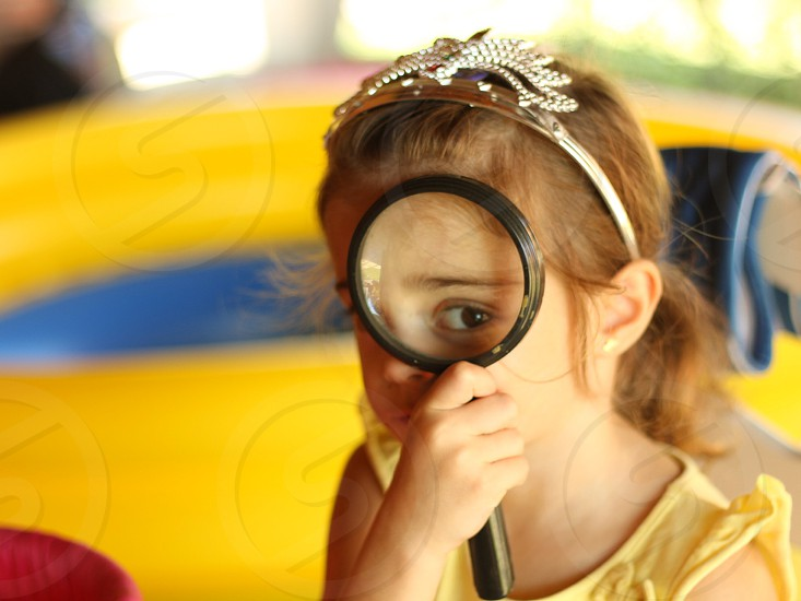 girl in yellow sleeveless blouse holding black magnifying glass photo
