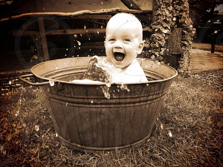 A baby splashing and laughing while having a bath in a big metal bucket. photo