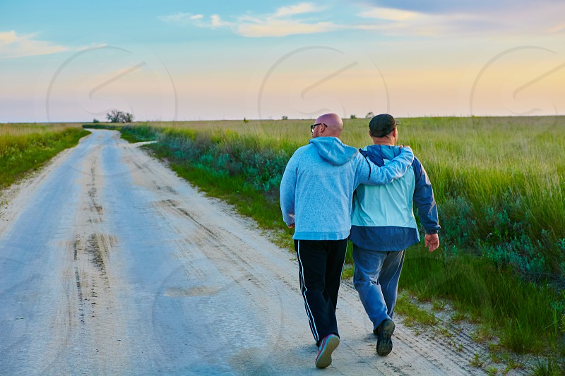 hairless man walking with a black haired man on gray road under a clear sky photo
