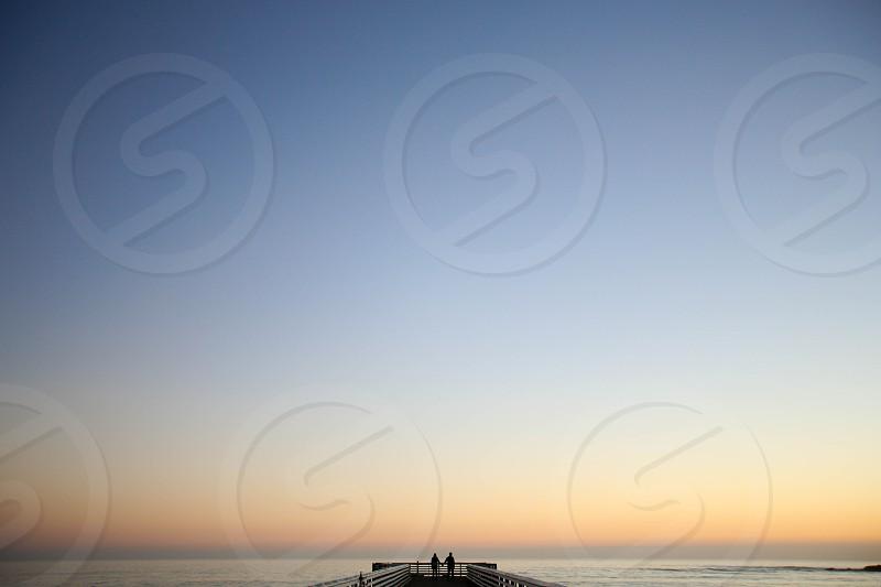 sunset silhouette beach pier ocean symmetry photo