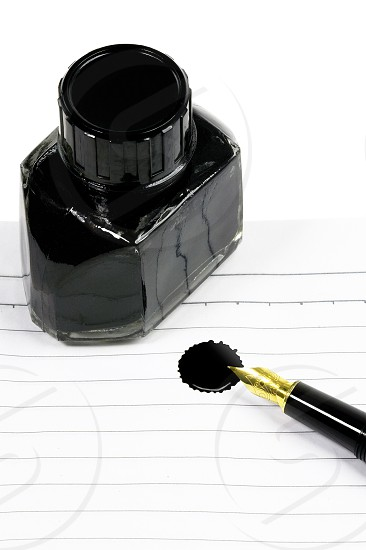classic black fountain pen on open notebook with ink bottle with stain on page photo