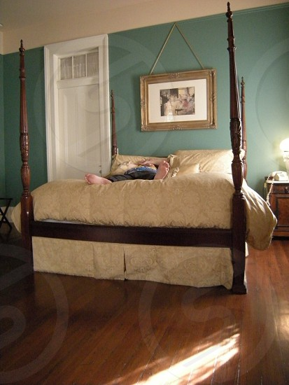 Man's feet on fluffy four poster bed photo