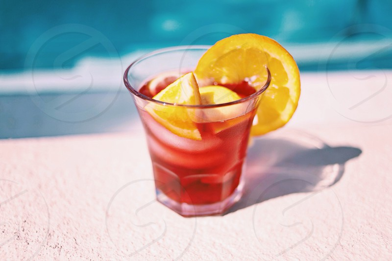 clear drinking glass with red liquid and yellow lemon photo