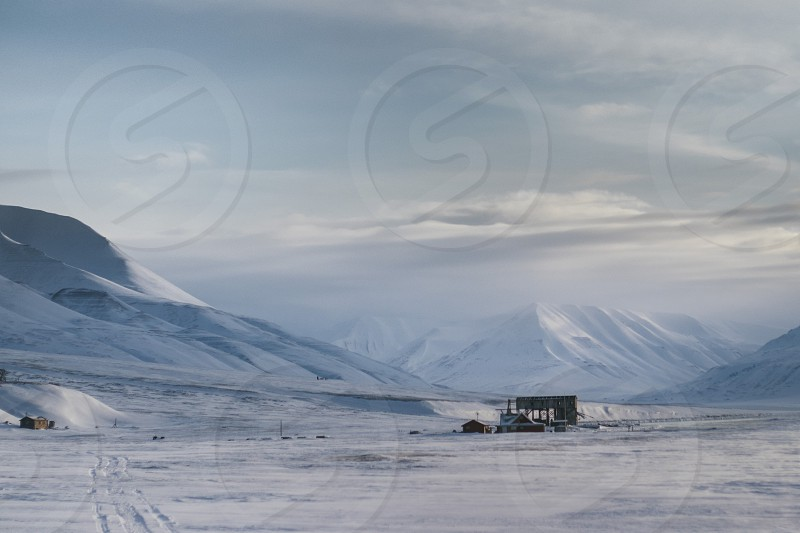 arctic polar circle mountains snow reindeer cabin hut clouds snow ice peaks animals northern north northern cold icy photo